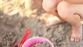 Het spelen van het meisje in het zand stock footage