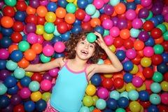 Het spelen van het meisje in kleurrijke ballenspeelplaats royalty-vrije stock foto's