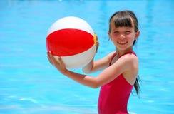 Het spelen van het meisje met bal in pool royalty-vrije stock afbeelding
