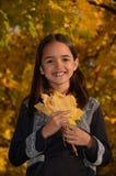 Het spelen van het meisje met bladeren Stock Afbeeldingen