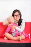 Het spelen van het meisje met een pop Stock Foto