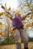 Het spelen van het meisje met gevallen bladeren in een de herfstpark stock foto