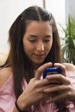 Het spelen van het meisje met haar mobiele telefoon Stock Fotografie