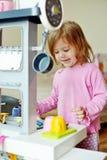 Het spelen van het meisje met keuken Stock Afbeelding