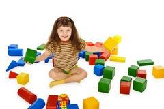 Het spelen van het meisje met kleurenkubussen op vloer Stock Afbeelding