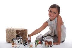 Het spelen van het meisje met stuk speelgoed dieren Stock Afbeelding