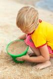 Het spelen van het meisje op een strand Stock Foto's