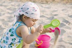 Het spelen van het meisje op het strand Stock Afbeelding