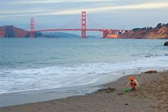 Het spelen van het meisje op het strand bij zonsondergang en de Gouden Brug van de Poort stock fotografie