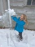 Het spelen van het meisje in sneeuw Royalty-vrije Stock Afbeeldingen