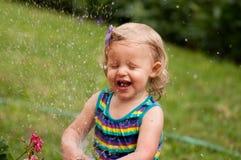 Het spelen van het meisje in water Stock Foto