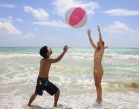 Het spelen van het paar met een bal bij het strand Stock Afbeeldingen