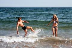 Het spelen van het paar in oceaanwater Stock Foto