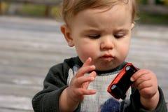 Het Spelen van Little Boy met zijn Auto stock foto