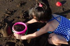 Het spelen van het meisje bij het strand stock foto's