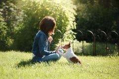 Het spelen van het meisje met een hond Jack Russell Terrier in aard De zomer stock foto