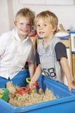 Het Spelen van twee Young Boys samen in Sandpit Stock Afbeelding