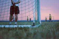 Het spelen van voetbal op een gebied bij zonsondergang Stock Foto's