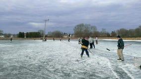 Het spelen van wat openluchtvijverhockey in de winter stock afbeeldingen
