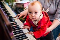 Het spelpiano van de babyjongen, gelukkig kinderjarenogenblik stock fotografie