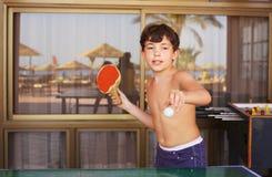 Het spelpingpong van de Preteen knap jongen in het hotel van de strandtoevlucht stock foto