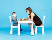 Het spelschaak van de moeder en van de zoon Familie en onderwijsconcept Stock Afbeelding