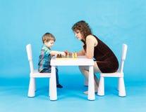 Het spelschaak van de moeder en van de zoon Familie en onderwijsconcept Stock Foto's