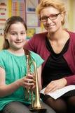 Het Speltrompet van leraarshelping pupil to in Muziekles stock afbeeldingen
