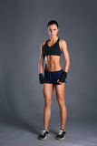 Het spier jonge vrouw stellen in sportkleding tegen zwarte achtergrond royalty-vrije stock foto's