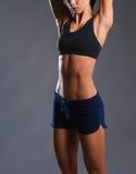 Het spier jonge vrouw stellen in sportkleding tegen zwarte achtergrond Stock Afbeelding