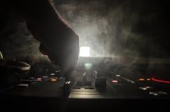 Het Spinnen van DJ, het Mengen zich, en het Krassen in een Nachtclub, Handen van DJ knijpen diverse spoorcontroles op het dek van stock foto