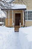 Het spoor van de sneeuw aan de plattelandshuisjedeur Stock Afbeelding