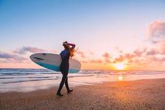 Het sportieve brandingsmeisje gaat naar het surfen Vrouw met surfplank en zonsondergang of zonsopgang op oceaan Royalty-vrije Stock Afbeeldingen