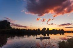 Het sportieve die mens kayaking op rivier door bos bij zonsondergang wordt omringd Stock Afbeeldingen