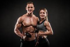 Het sportieve jonge paar stellen op zwarte achtergrond royalty-vrije stock foto