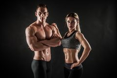 Het sportieve jonge paar stellen op zwarte achtergrond stock foto's