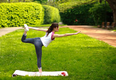 Het sportieve jonge vrouw uitrekken zich, die oefeningen het in evenwicht brengen doen Royalty-vrije Stock Foto's