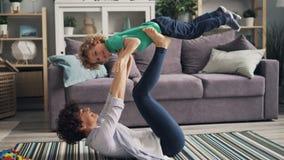 Het sportieve mamma spelen met kind die hem opheffen met handen en benen die op vloer liggen stock video