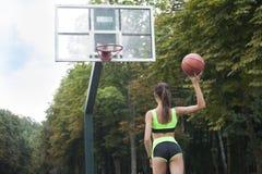 Het sportieve meisje gaat en werpt de bal achteruit in de ring Royalty-vrije Stock Afbeelding