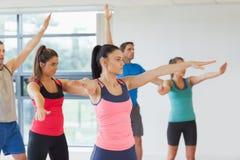 Het sportieve mensen uitrekken zich uit overhandigt bij yogaklasse Stock Foto's