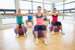 Het sportieve mensen uitrekken zich uit overhandigt op oefeningsballen bij gymnastiek Stock Afbeeldingen
