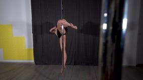 Het sportieve sexy jonge meisje spint en doet een acrobatische truc stock video