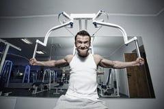 Het sportieve sexy mens stellen in gymnastiek Stock Foto