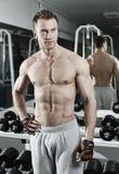 Het sportieve sexy mens stellen in gymnastiek Stock Afbeeldingen