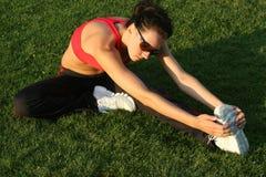 Het sportieve vrouw uitrekken zich Stock Afbeeldingen