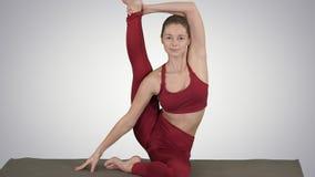Het sportieve yogimeisje die geschiktheidspraktijk, rek, yogaasana Parivritta Kraunchasana, Reiger doen stelt op gradiënt stock video