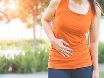 Het sportmeisje heeft maagpijn na het aanstoten van het werkou stock afbeeldingen