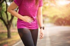 Het sportmeisje heeft maagpijn nadat het aanstoten in park uitwerkt Het concept van de gezondheidszorg stock afbeelding