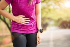 Het sportmeisje heeft maagpijn nadat het aanstoten in park uitwerkt Het concept van de gezondheidszorg royalty-vrije stock fotografie