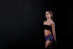 Het sportmeisje houdt zich en kijkt op zwarte achtergrond afzijdig stock foto